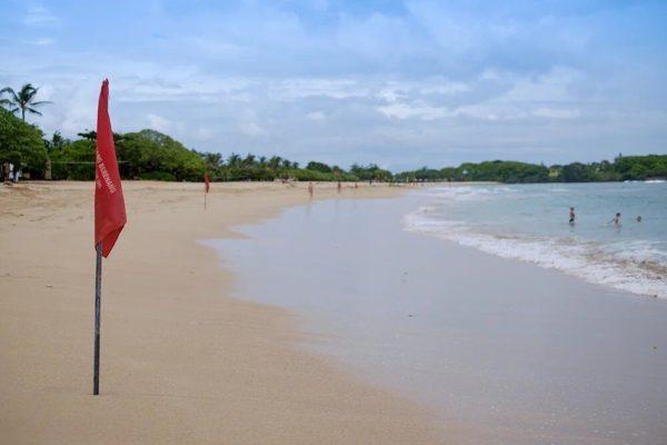 Красные флаги на пляже острова Бали